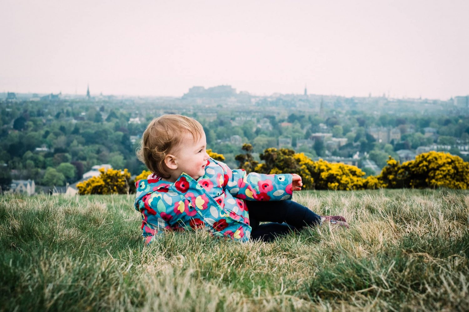 Toddler lying on Blackford Hill with Edinburgh Castle in background, Scotland