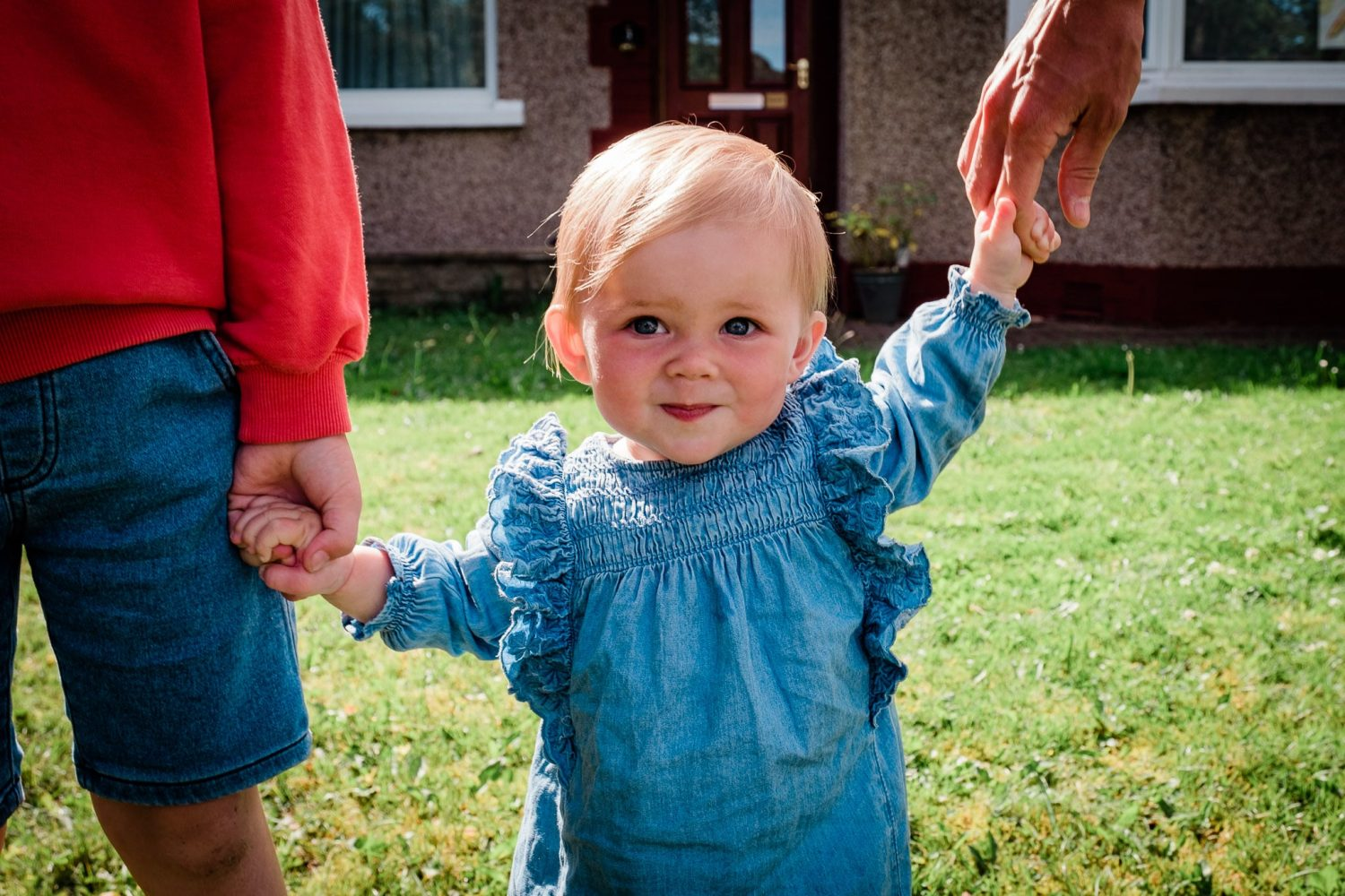 Sweet little girl walking hand in hand with brother and dad