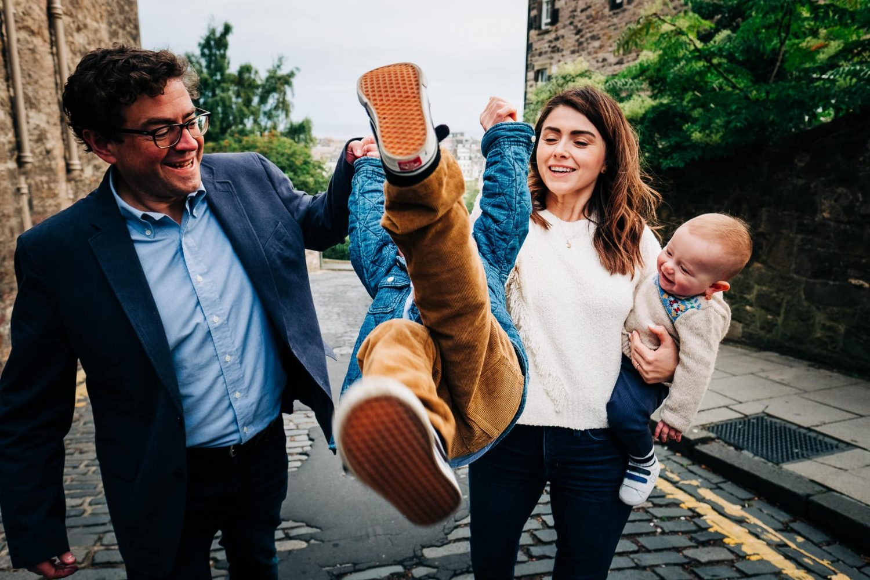Mum and dad swing their son in the air in Edinburgh, Scotland