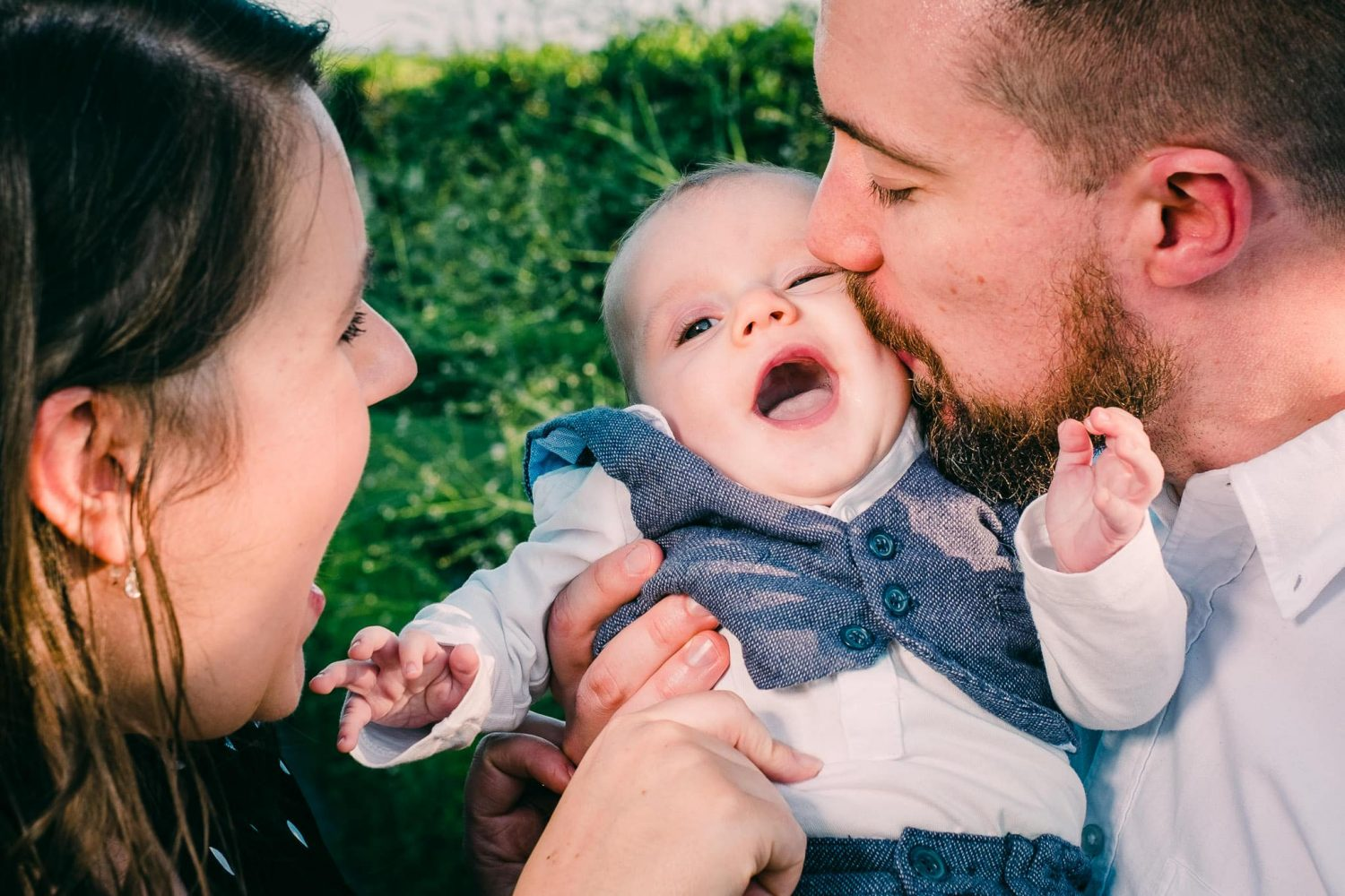 Baby boy being kissed by both parents simultaneously in Greywalls Hotel Garden